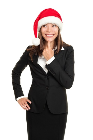 asian woman face: christmas business woman thinking looking to the side wearing santa hat and business suit. Multi-racial santa businesswoman isolated on white background. Stock Photo