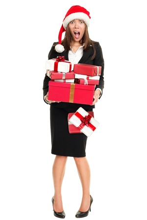 holiday spending: Stress christmas shopping business woman holding many gifts busy for holidays. Full length isolated on white young asian caucasian businesswoman.