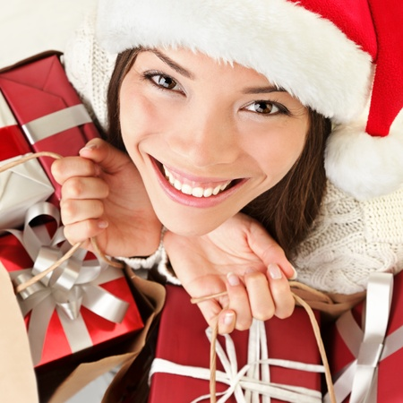 happy shopper: Christmas gifts santa woman shopping. Closeup portrait of young woman holding christmas presents in shopping bags. Beautiful smiling happy santa girl wearing santa hat.
