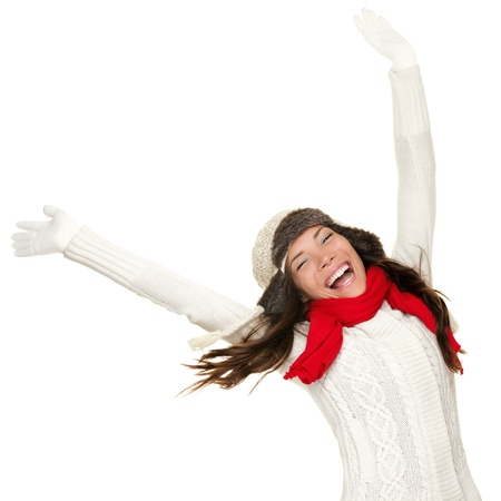 ecstatic: Winter fun woman winner and success concept. Cheering happy ecstatic female model with arms up celebrating winning something. Multicultural Caucasian Asian winter girl isolated on white background. Stock Photo