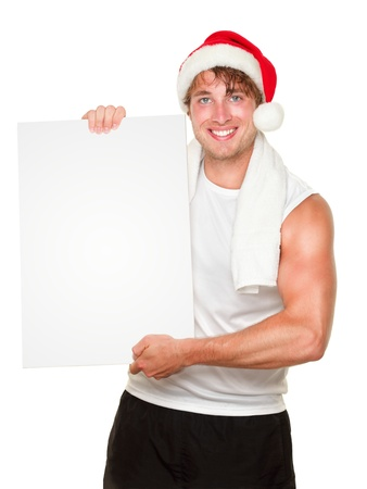 Fitness man holding sign wearing christmas santa hat. Fit male fitness model isolated on white background.