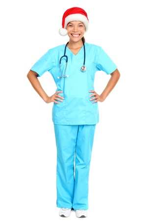 nurse or young doctor wearing christmas santa hat smiling happy standing isolated on white background in full body wearing scrubs. Beautiful multicultural Asian Caucasian female medical professional. photo