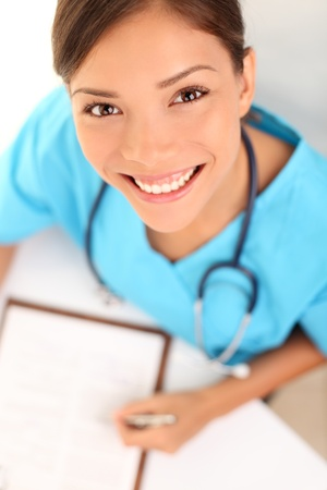 nurse clipboard: Nurse or woman doctor. Young female medical professional close up portrait. Multi-racial Asian Caucasian model wearing blue srubs and stethoscope from high angle view.
