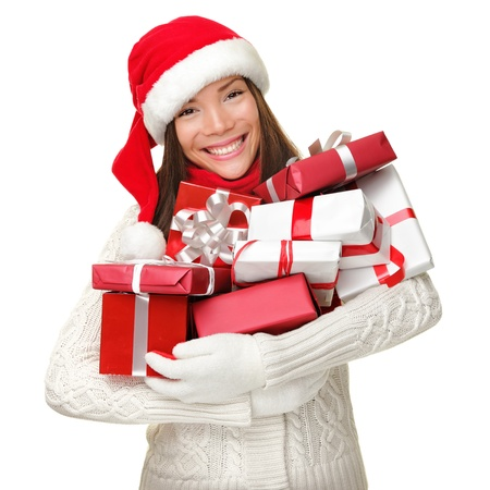 Christmas shopping woman holding many Christmas gifts in her arms wearing santa hat and winter clothing. Beautiful young female model isolated on white background.