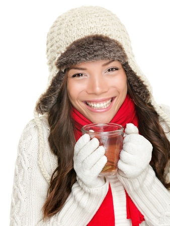 winter woman drinking tea wearing warm winter clothing, sweater, gloves and scarf. Beautiful mixed race asian caucasian girl model isolated on white background. photo