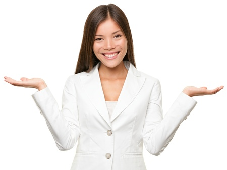 shrugging: Showing business woman with empty copy space for two products with open hand palms. Businesswoman in white suit isolated on white background. Happy smiling multiracial Chinese Asian  Caucasian female model. Stock Photo