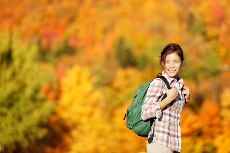 Hiking woman in Fall forest. Female hiker looking around in forest in autumn colors. Beautiful young woman on hike.