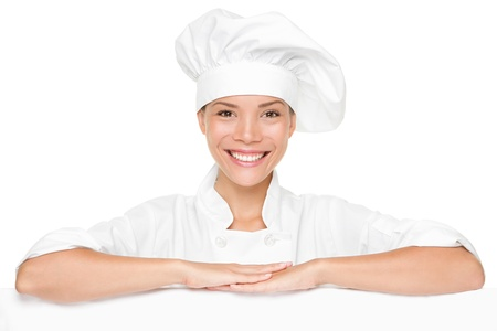 bakers: Chef or baker woman showing blank empty billboard sign. Beautiful smiling happy chef leaning on placard banner with copy space for menu or other text. Stock Photo