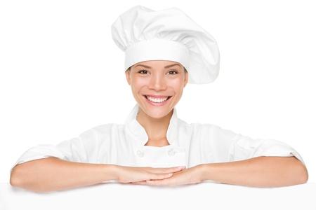 panadero: Mujer chef o baker mostrando signos de billboard vacía en blanco. Hermosa chef feliz sonriente apoyándose en banner de cartel con espacio de copia de menú u otro texto.