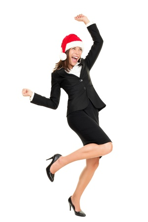 Christmas business woman wearing santa hat dancing happy and excited standing in full body. Beautiful smiling cheerful mixed race Asian Caucasian female businesswoman isolated on white background. Stock Photo