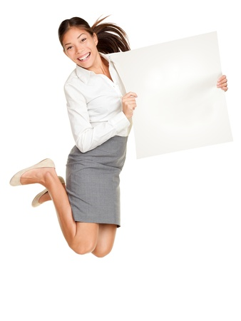 celebrating: Showing sign. Woman jumping holding poster of paper, blank and empty with copy space. Casual business woman jumping excited smiling happy and cheerful isolated on white background.