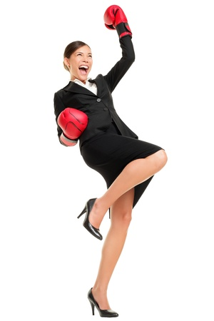Winning business woman celebrating wearing boxing gloves and business suit. Winner and business success concept photo of young multiracial Asian Caucasian businesswoman isolated on white background.