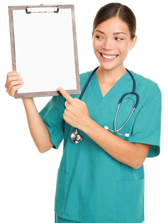 Nurse showing clipboard sign with blank paper for copy space. Ethnic Chinese Asian / Caucasian female nurse or young doctor wearing scrubs and stethoscope isolated on white background. Stock Photo - 10916742