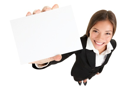 business woman standing: Showing sign - woman holding big business card  paper sign with lots of copy space. Sign and businesswoman face both in focus, High angle full lengh view of happy smiling mixed race Asian  Caucasian female businesswoman isolated on white background. Stock Photo