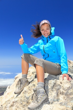 Hiker woman at mountain top summit enjoying view giving success thumbs up sign smiling happy of her hiking achievement. Beautiful happy smiling female hiker on the top of volcano Teide, Tenerife, Spain. photo
