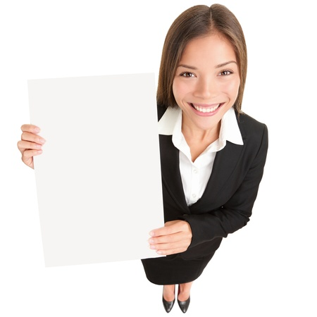 Business woman showing sign. Young Asian businesswoman in suit showing blank sign poster with copy space. Beautiful young female model isolated on white background in full length. Stock Photo - 10916749