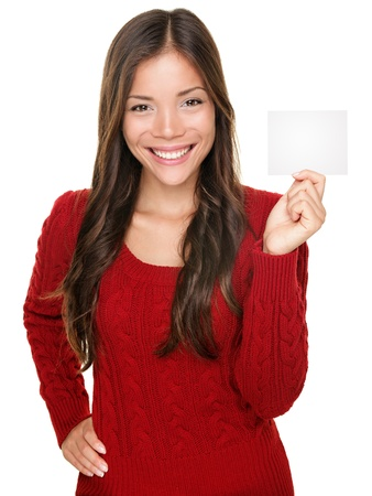 showing woman presenting blank gift card sign. Happy smiling Asian woman in red winter sweater isolated on white background. Stock Photo