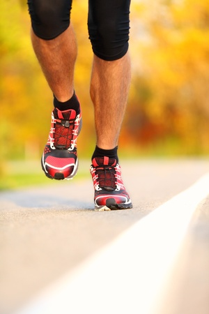 Running shoes on runner outdoors. Closeup of man jogging and training for marathon. photo