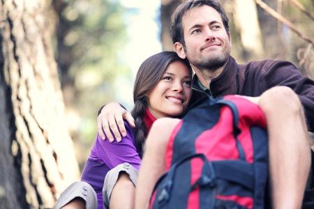 parejas felices: Pareja feliz sentado junto al aire libre durante los viajes de excursión. Interracial pareja activa.