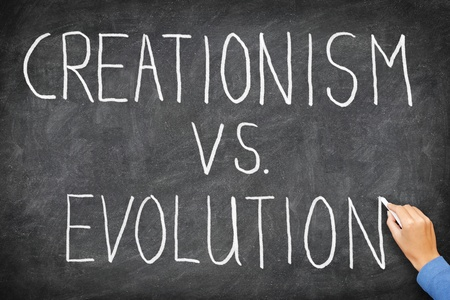 darwin: Creationism vs evolution. Religion and education concept. Hand writing on blackboard. Stock Photo