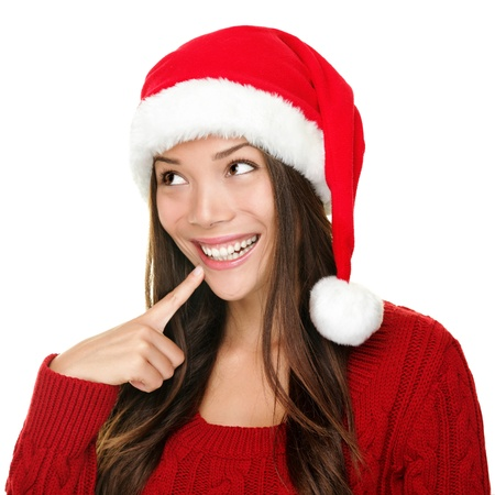 looking sideways: santa christmas woman looking to the side thinking happy and playful. Asian christmas girl wearing santa hat and red sweater isolated on white background.