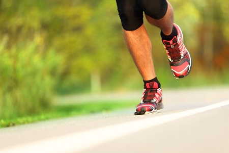 athlete running: Runner - running shoes closeup. Man jogging and training for marathon outdoor in park.