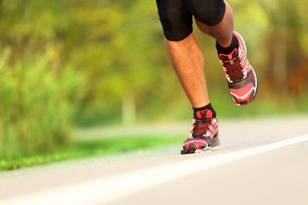 Runner - corriendo de cerca los zapatos. El hombre de jogging y la formación de maratón al aire libre en el parque.