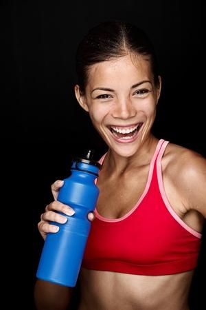 sudoracion: Fitness sonriente con la energía feliz fresco mientras que la sudoración y el agua potable de la botella mujer. Blanco modelo chino asiático  caucásico femenino sobre fondo negro.