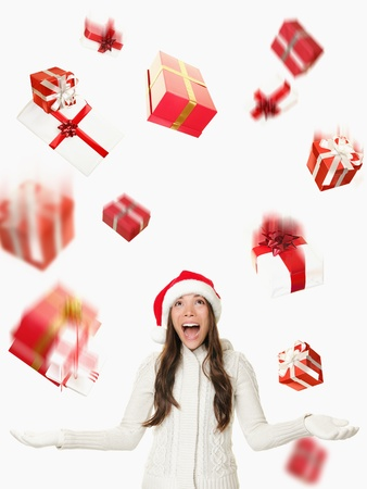 is raining: Christmas Santa woman - raining gifts and falling presents. Asian woman in santa hat excited isolated on white background.