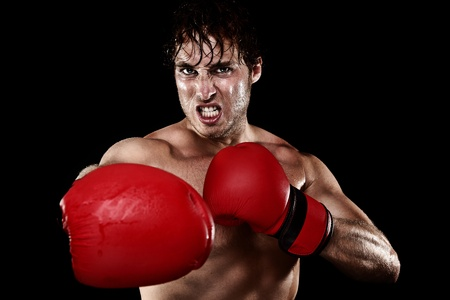 Boxing boxer. Man with boxing gloves hitting and punching looking angry. Strong muscular fit fitness model showing competition strength. Caucasian male model isolated on black background. photo
