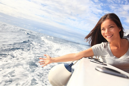 Boat woman smiling happy looking at the sea sailing by. Asian  Caucasian female model.