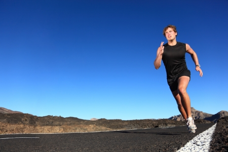 atleta: Running man. Male runner at sprinting speed training for marathon outdoors in amazing volcanic dessert landscape. Strong and fit caucasian male fitness model.
