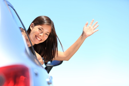 Car woman happy waving smiling at camera popping head out the window. New car, road trip vacation or drivers licence concept. Beautiful young mixed race Chinese Asian  white Caucasian woman. photo