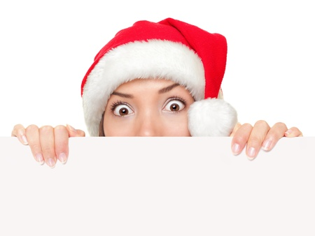 mrs  claus: Christmas sign woman peeking over empty blank paper sign wearing santa hat isolated on white background. Funny surprised and shocked look on santa girl face.