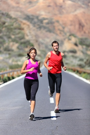 Couple running. Two runners training for marathon run outdoors on road in beautiful landscape. Man Caucasian runner and Asian woman runner. photo