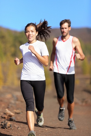 caucasian race: Young couple running together outdoors in beautiful volcanic landscape. Woman trail runner training for marathon run with male model jogging in background.