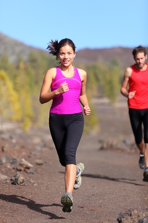 Running woman with male runner in background trail running training for marathon in volcanic landscape. Mixed race Chinese Asian  Caucasian woman jogging. photo
