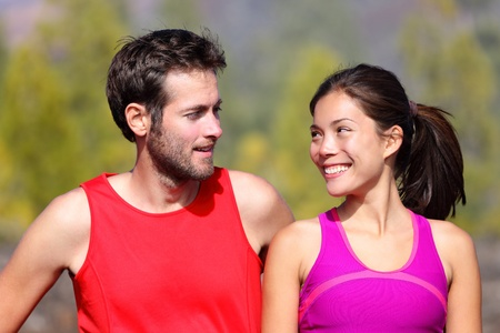 Happy sporty couple portrait. Runners outside resting after running. Man and woman smiling at each other. Asian female athlete and white caucasian male model. photo