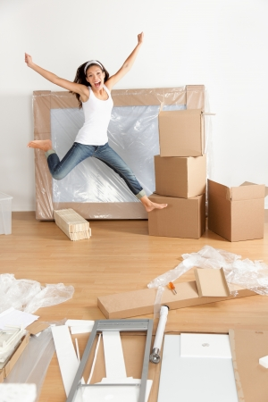unpacking: New home - moving woman excited and happy jumping of joy with moving boxes. Young Asian Caucasian woman. Stock Photo