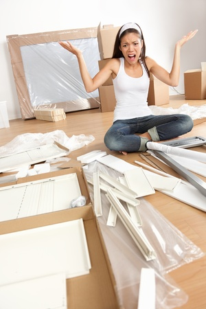 assembling: Furniture assembly frustration - woman moving in new home trying to assemble table. Funny photo of multiracial Asian Caucasian young woman.