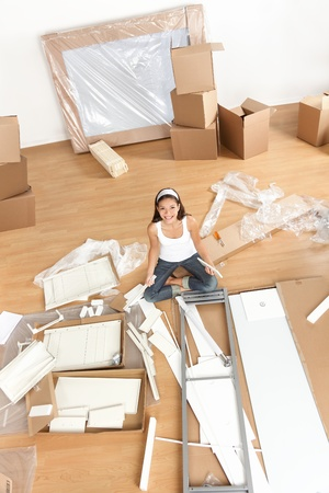 Moving woman in new home sitting on floor unpacking and assembling furniture.  Multiracial Asian Caucasian young woman. photo