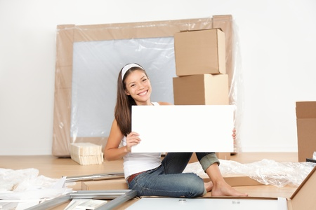assembling: Moving sign woman. Woman moving in new home unpacking showing blank white sign while doing furniture assembly of new table. Beautiful young mixed race Asian Caucasian young woman in new apartment condo.