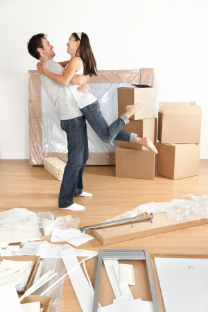 relocating: Couple moving in happy and excited in new home. Young interracial couple with moving boxes and furniture assembly in new house or apartment. Caucasian man and Asian woman embracing.