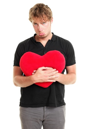 relationship breakup: Unhappy love. Funny image of sad broken heart valentines day man holding red heart isolated on white background.