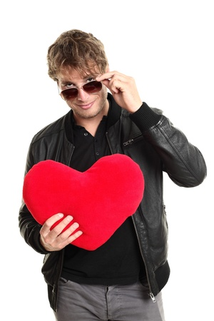 seducing: Valentines day man player holding heart looking over sunglasses. Funny image of caucasian male in leather jacket isolated on white background.