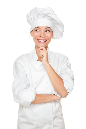 Chef thinking looking smiling and happy to the side. Woman chef, cook or baker in chef uniform and hat. Young asian female isolated on white background. photo