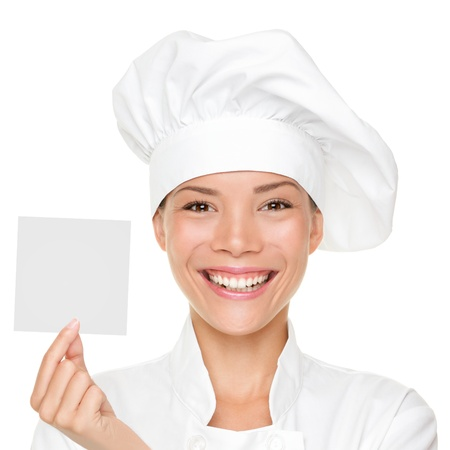 Chef, baker or cook woman showing blank sign card wearing chefs uniform and hat. Blank card for menu, gift card, offer etc. Beautiful young multicultural Asian  Caucasian female woman isolated on white background.