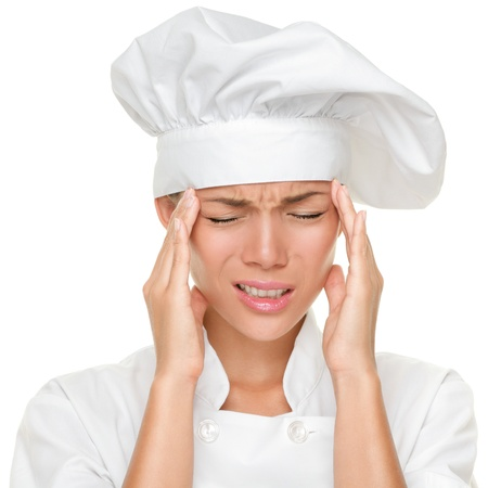 health issue: Chef headache and stress at work. Woman baker, chef or cook tired stressed and overworked with stress. Closeup of Asian Caucasian female isolated on white background.