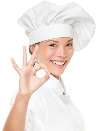 Chef-kok bakker of kok laten zien ok handteken naar perfectie. Vrouw chef-kok lacht blij en trots. Portret van vrouwelijke kok het dragen van chef-koks hoed op een witte achtergrond. Gemengd ras Aziatische Kaukasische vrouwelijk model.