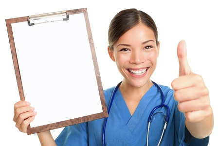 Nurse showing blank clipboard sign smiling happy giving thumbs up success sign wearing stethoscope and scrubs. Multicultural Asian Caucasian female nurse or young doctor isolated on white background. Stock Photo